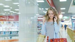 Una mujer atractiva con los panieres que camina en la alameda, hablando en el teléfono móvil almacen de video