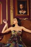 Una mujer atractiva con un retrato en el fondo Fotos de archivo