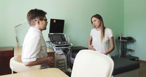 Una mujer atractiva consulta a un doctor en un cuarto del diagnóstico del ultrasonido almacen de metraje de vídeo