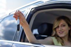 Una mujer atractiva en un coche consigue las llaves del coche Alquiler o compra del auto Imagen de archivo libre de regalías