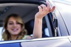 Una mujer atractiva en un coche consigue las llaves del coche Alquiler o compra del auto Fotografía de archivo
