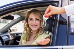 Una mujer atractiva en un coche consigue las llaves del coche Alquiler o compra del auto Imágenes de archivo libres de regalías