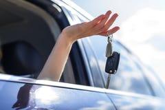 Una mujer atractiva en un coche consigue las llaves del coche Alquiler o compra del auto Foto de archivo libre de regalías