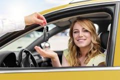 Una mujer atractiva en un coche consigue las llaves del coche Alquiler o compra del auto Fotos de archivo