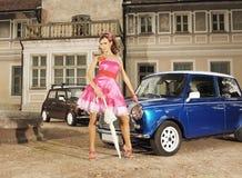 Una mujer atractiva en un vestido que presenta cerca de un coche imagen de archivo libre de regalías