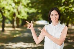 Una mujer atractiva en una mujer alegre verde del bosque A en un fondo brillante Una muchacha que señala y que presenta, y pareci Fotos de archivo