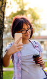 Una mujer atractiva joven que hace un autorretrato y que sostiene una taza de café Foto de archivo libre de regalías