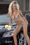 La muchacha atractiva lava el coche negro en bikini Imagenes de archivo