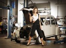 Una mujer atractiva que repara un coche en un garaje fotos de archivo