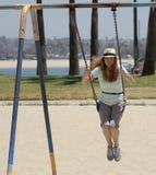 Una mujer balancea en un parque por una bahía Foto de archivo libre de regalías