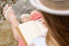 Una mujer bastante europea es sittin en una piedra c y escritura de cierta idea, letra o trabajo al lado de pluma en su cuaderno Imágenes de archivo libres de regalías