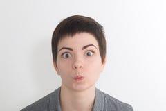 Una mujer bastante joven mira el espectador con los labios encaramados que soplan el aire o un beso en la cámara Foto de archivo libre de regalías