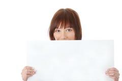 Una mujer bastante joven que lleva a cabo una muestra en blanco Imagenes de archivo