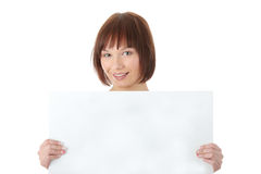 Una mujer bastante joven que lleva a cabo una muestra en blanco Imagen de archivo libre de regalías