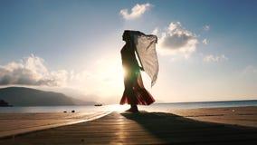 Una mujer bonita con una bufanda se coloca en la costa en la salida del sol en la cámara lenta metrajes