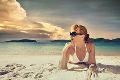Una mujer bonita en bikini que toma el sol en la playa en un fondo Foto de archivo