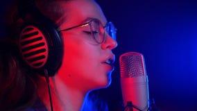 Una mujer bonita joven en vidrios y auriculares que canta en el estudio