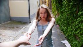 Una mujer bonita joven lleva a su novio por una mano a través de una calle metrajes