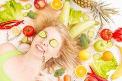 Una mujer bonita joven rodeada por las verduras y las frutas imagenes de archivo