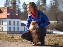 Una mujer bonita que camina su perro del perro de Pomerania foto de archivo libre de regalías