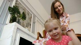 Una mujer bonita trenza la trenza de su pequeña hija metrajes
