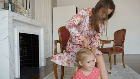 Una mujer bonita trenza la trenza de su pequeña hija almacen de video