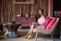 Una mujer bronceada encantadora se sienta en un sof? rosado con un libro en sus manos presentaci?n y sonrisa imagen de archivo