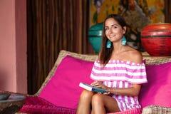 Una mujer bronceada encantadora se sienta en un sof? rosado con un libro en sus manos presentaci?n y sonrisa Cierre para arriba fotos de archivo