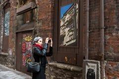 Una mujer cabelluda gris toma las imágenes de la decoración en una calle innomada cerca de los comerciantes Caffe en Seattle fotos de archivo