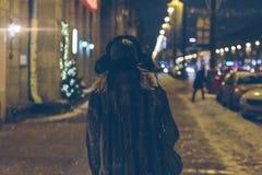 Una mujer camina abajo de la calle en la noche Fotos de archivo