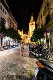 Una mujer camina abajo de las calles de Sevilla, España en la noche fotos de archivo