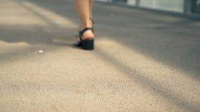 Una mujer camina en un puente elevado Las piernas de una mujer en sandalias almacen de video