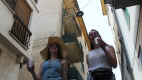 Una mujer camina entre los edificios en un callejón Entonces otra mujer aparece metrajes