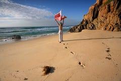 Una mujer camina a lo largo de la playa, del viaje, de la salud y del bienestar Imagen de archivo