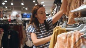 Una mujer camina por una tienda de ropa y escoge nuevas cosas metrajes