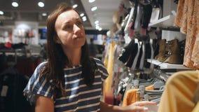 Una mujer camina por una tienda de ropa y escoge nuevas cosas almacen de video