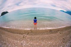 Una mujer camina solamente en la costa de mar fotografía de archivo