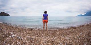 Una mujer camina solamente en la costa de mar fotografía de archivo libre de regalías