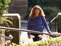 Una mujer camina a través de una entrada del jardín Imagenes de archivo