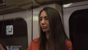 Una mujer cansada en devoluciones de un traje a casa en tren tarde en la noche almacen de metraje de vídeo
