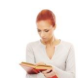Una mujer caucásica del pelirrojo joven que sostiene los libros Imagenes de archivo