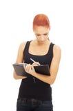 Una mujer caucásica del redhead joven que escribe a un libro Fotos de archivo