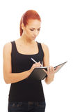 Una mujer caucásica del redhead joven que escribe a un libro Imágenes de archivo libres de regalías