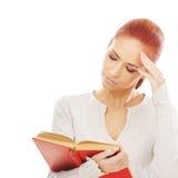 Una mujer caucásica del redhead joven que lee un libro Fotografía de archivo libre de regalías