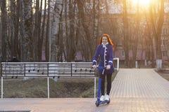 Una mujer caucásica joven con el pelo rojo en una capa azul rueda o monta rápidamente una vespa eléctrica azul en el parque Eco fotografía de archivo