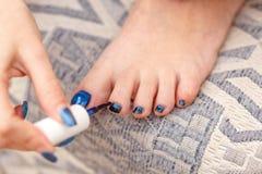 Una mujer caucásica joven pinta sus uñas del pie fotos de archivo libres de regalías