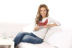 Una mujer caucásica joven que lee un libro en un sofá Imagenes de archivo