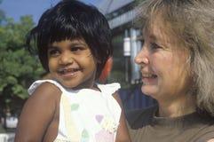 Una mujer caucásica que detiene a un niño indio, Chevy Chase, Doctor en Medicina foto de archivo