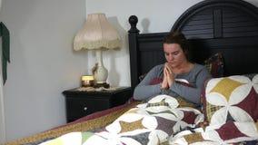 Una mujer caucásica que ruega en su cama - concepto del cristianismo metrajes