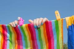 Una mujer colgó el lavadero lavado al aire libre Lavadero de sequía de la muchacha en una línea de ropa en el sol en el al aire l Fotos de archivo